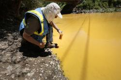 In this Aug. 6, 2015 file photo, Dan Bender, with the La Plata County Sheriff's Office, takes a water sample from the Animas River near Durango, Colo. after the accidental release of an estimated 3 million gallons of waste from the Gold King Mine