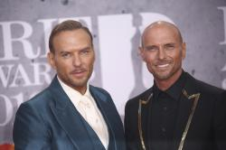 Musicians Matt Goss, left, and Luke Goss poses for photographers upon arrival at the Brit Awards in London.
