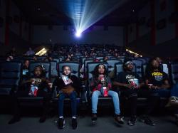 "Mari Copeny, third from left, watches a free screening of the film ""Black Panther"" with more than 150 children, after she raised $16,000 to provide free tickets in Flint Township, Mich."