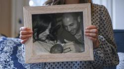 Lindsey Schmitz holds a framed photo of her stillborn son, Sawyer, being cuddled by her and her husband, Andrew.