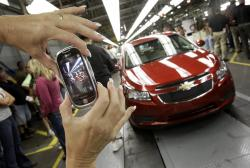 In this Sept. 8, 2010, file photo, an auto worker takes a picture of the first Chevrolet Cruze compact sedan to come off the assembly line at a ceremony inside the GM factory in Lordstown, Ohio.
