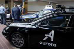 Pittsburgh Mayor William Peduto, left, checks out autonomous vehicles designed by Aurora Innovations, front, and Argo AI, rear, after signing an executive order outlining objectives and expectations for the safe testing and development of autonomous vehicles in Pittsburgh, Monday, March 4, 2019