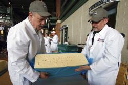 Steve Stettler (left) and Bruce Workman (right) cut a piece a swiss at the United States Championship Cheese Contest.