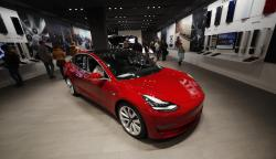 In this Feb. 9, 2019, file photograph, buyers look over a Model 3 in a Tesla store in Cherry Creek Mall in Denver