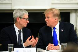 President Donald Trump talks to Apple Inc. CEO Tim Cook during the American Workforce Policy Advisory Board's first meeting in the State Dining Room of the White House in Washington.