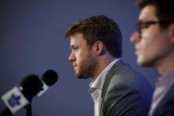 Toronto Maple Leafs defenseman Morgan Rielly, left, and general manager Kyle Dubas pause during a press conference, Tuesday, March 12, 2019, in Toronto, as they address an NHL investigation into an alleged slur used during an NHL hockey game the night before against the Tampa Bay Lightning