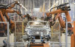 In this Saturday, March 9, 2019 file photo robots work on a VW Passat car at a plant of the car manufacturer Volkswagen in Emden, Germany