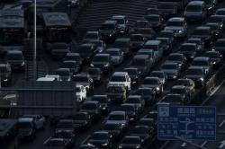 In this Dec. 11, 2018, file photo, a beam of sunlight is cast on vehicles on a city ring-road clogged with heavy traffic during the morning rush hour in Beijing.