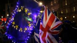 Anti-Brexit, remain in the European Union supporters hold an EU and British union flag outside the Houses of Parliament in London, Wednesday, March 13, 2019