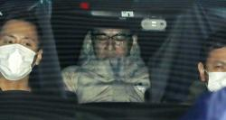 In this March 13, 2019, photo, Japanese musician Pierre Taki in a police car is sent to a police station in Tokyo.