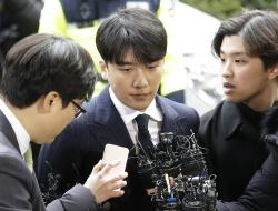 Seungri, center, member of a popular K-pop boy band Big Bang, arrives at the Seoul Metropolitan Police Agency in Seoul, South Korea, Thursday, March 14, 2019