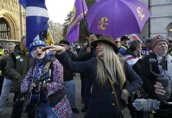 An anti-Brexit remain in the European Union supporter, left, plays a guitar as she's surrounded by UKIP pro-Brexit supporters outside the Houses of Parliament in London, Thursday, March 14, 2019.