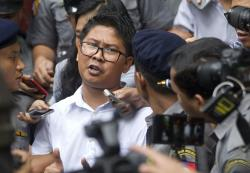In this Sept. 3, 2018 file photo, Reuters journalist Wa Lone, center, talks to journalists while he is escorted by polices as they leave the court in Yangon, Myanmar.
