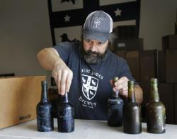 Jamie Adams shows some intact beer bottles recovered from the shipwreck of the SS Oregon at his St. James Brewery in Holbrook, N.Y