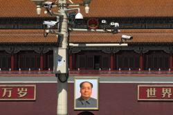 Surveillance cameras are mounted on a lamp post near the large portrait of Chinese leader Mao Zedong at the Tiananmen Gate in Beijing, Friday, March 15, 2019.