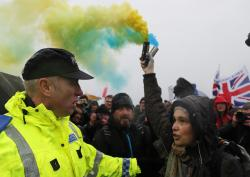 A pro European Union demonstrator releases flares to protest the start of the first leg of March to Leave the European Union, in Sunderland, England, Saturday, March 16, 2019.