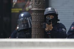 Riot police officers take position during a yellow vests demonstration on the Champs Elysees avenue Saturday, March 16, 2019 in Paris.