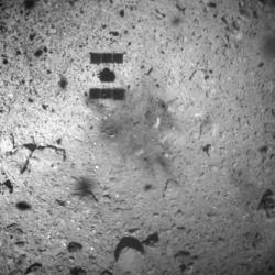 In this Feb. 22, 2019, file photo, this image released by the Japan Aerospace Exploration Agency (JAXA) shows the shadow, center above, of the Hayabusa2 spacecraft after its successful touchdown on the asteroid Ryugu.
