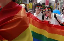 Participants smile as they march with a banner during the Tokyo Rainbow Pride parade celebrating the LGBT community in Tokyo's Shibuya district.