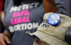 A Planned Parenthood supporter hosts an abortion rights button on her hat during a rally.