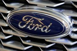 This Feb. 15, 2018, file photo shows a Ford logo on the grill of a car on display at the Pittsburgh Auto Show