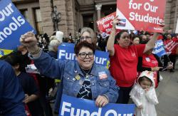 In this March 11, 2019, photo, Dr. Nancy Vera, center, of Corpus Christi, Texas, joins other educators during a rally to support funding for public schools in Texas at the state Capitol in Austin, Texas
