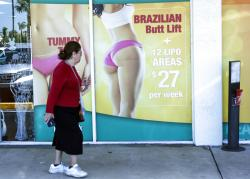 A window display advertises low-cost comestic procedures outside surgery clinic in Miami.
