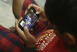 An Indian boy plays an online game PUBG on his mobile phone in Hyderabad, India, Friday, April 5, 2019