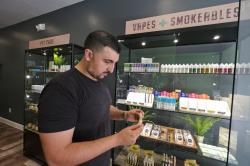 Gus Dabais looks over CBD products he sells at his Sidewalk Wellness store in San Francisco.