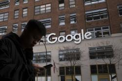 In this Dec. 17, 2018, file photo, a man using a mobile phone walks past Google offices in New York