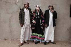 An Egyptian student borrows a Bedouin wedding dress to pose for a photograph with Bedouin men from the Hamada tribe, in Wadi Sahw, Abu Zenima, in South Sinai, Egypt