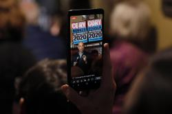 In this Feb. 9, 2019, file photo, Sen. Cory Booker, D-N.J., is seen on a cell phone as he speaks during a meet and greet with local residents in Marshalltown, Iowa