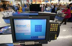 This Nov. 9, 2018, file photo shows a checkout scanner at a Walmart Supercenter in Houston. Walmart says it's buying San Francisco-based ad tech startup Polymorph Labs as it looks to better compete with online rival juggernaut Amazon in targeting shoppers online
