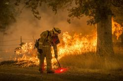 In this July 28, 2018, photo, a Cal Fire firefighter creates a back burn on Cloverdale Road near Redding, Calif., during the Carr Fire
