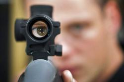 In this Sept. 15, 2010 file photo, an employee looks through the scope of long gun at a gun store in Calgary, Alberta, Canada
