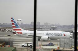 In a March 13, 2019 file photo, an American Airlines Boeing 737 MAX 8 sits at a boarding gate at LaGuardia Airport in New York.