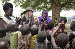 In this photo taken Tuesday, April 2, 2019, human rights activist Mia Farrow, center-left, plays a game with children during a visit to an internally displaced person's camp in the capital Juba, South Sudan.