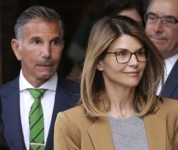 In this April 3, 2019 file photo, actress Lori Loughlin, front, and husband, clothing designer Mossimo Giannulli, left, depart federal court in Boston