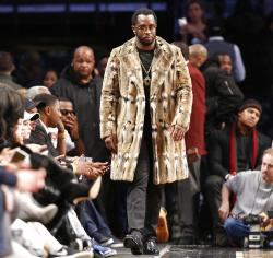 """Sean """"Diddy"""" Combs, wearing a fur coat, walks down the sideline during the second half of an NBA basketball game between the Brooklyn Nets and the New York Knicks in New York."""