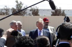 In this April 5, 2019, file photo, President Donald Trump visits a new section of the border wall with Mexico in Calexico, Calif.
