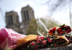 Flowers and tributes are left outside the Notre Dame Cathedral in Paris, Thursday, April 18, 2019