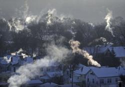 In this Wednesday Jan. 30, 2019, file photo smoke rises from the chimneys of homes in St. Paul, Minn.