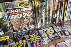 In this July 12, 2017 file photo, an issue of the National Enquirer featuring President Donald Trump on its cover is displayed on a newsstand in a store in New York.
