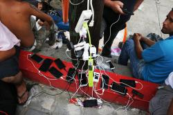 In this Oct. 28, 2018 file photo, migrants charge their cell phones as a caravan of Central Americans trying to reach the U.S. border halts for a rest day in San Pedro Tapanatepec, Oaxaca state, Mexico