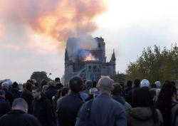 In this Monday, April 15, 2019 file photo, people watch as flames and smoke rise from Notre Dame cathedral in Paris