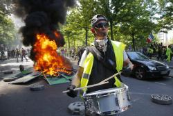 A man bangs a drum in front of a fire on the street during a yellow vest demonstration in Paris, Saturday, April 20, 2019