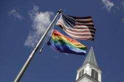 A gay pride rainbow flag flies along with the U.S. flag in front of the Asbury United Methodist Church in Prairie Village, Kan., on Friday, April 19, 2019