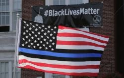 In this July 28, 2016, file photo, a flag with a blue and black stripes in support of law enforcement officers, flies at a protest by police and their supporters outside Somerville City Hall in Somerville, Mass.