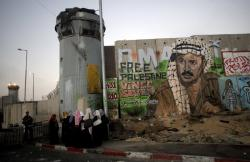 In this Friday, Aug. 13, 2010 file photo, Palestinian women wait near a section of Israel's separation barrier covered in graffiti, one depicting the late Palestinian leader Yasser Arafat, at the Qalandiya checkpoint , between Jerusalem and the West Bank city of Ramallah