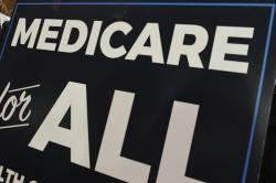 """In this April 10, 2019 file photo, a sign is shown during a news conference to reintroduce """"Medicare for All"""" legislation, on Capitol Hill in Washington"""